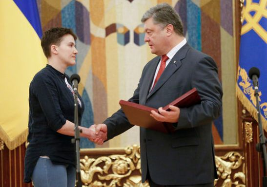Ukrainian President Petro Poroshenko, right, shakes hands with Ukrainian jailed pilot Nadezhda Savchenko, as he awards her with the Hero of Ukraine medal in the Presidential Office in Kiev, Ukraine, Wednesday, May 25, 2016. Russia has released jailed pilot Nadezhda Savchenko, as part of a swap for two Russian servicemen imprisoned in Ukraine. Russia has released jailed pilot Nadezhda Savchenko, as part of a swap for two Russian servicemen imprisoned in Ukraine. (AP Photo/Sergei Chuzavkov)